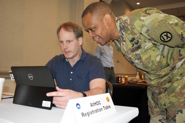 Lt. Col. Aaron Allen, right, visits the AtHOC emergency messaging system table during the emergency preparedness Community Information Exchange at the Camp Zama Community Club May 10. Joseph Kelley, left, a management analyst for the Directorate of Plans, Training, Mobilization and Security, helps him.