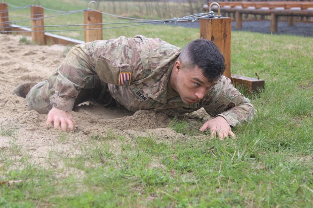 New York Army National Guard Cpl. Joseph Ryan, an assistant operations specialist with headquarters company, 1-69th Infantry Regiment, low crawls through an obstacle course during the 2019 Regional Best Warrior Competition at the Regional Training Institute in Center Strafford, NH, April 30. The event pits state best warrior winners from CT, MA, NH, NJ, NY, and RI to compete for the regional title.