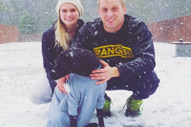 """U.S. Army 1st Lt. Jakub Walters poses for a picture in the snow with his wife Lexi and their """"fur baby"""" Pips.  (Photo courtesy 1st Lt. Jakub Walters)"""