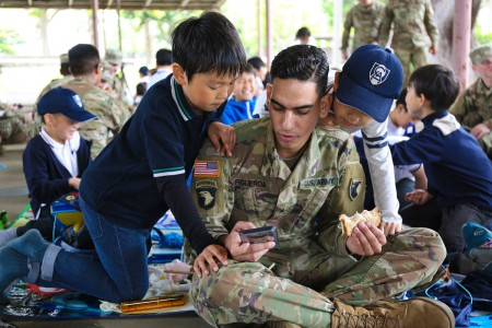A Soldier assigned to the 38th Air Defense Artillery Brigade, shows LCA Kokusai Elementary School students a game on his cellphone while eating lunch during an Earth Day event, April 24, at Sagami General Depot, Japan.