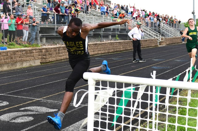Fort Knox Eagles runner Jatarrius Battle reaches for a dramatic first-place finish against Owensboro Catholic in the 4x400 relay. Fort Knox boys' pulled out a one point overall win against the Aces because of the victory.