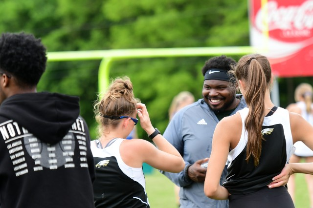 Fort Knox head coach Terry Turner has a lighthearted moment with two members of the girls' 4x400 relay team prior to their big win at the track and field regional championship tournament.