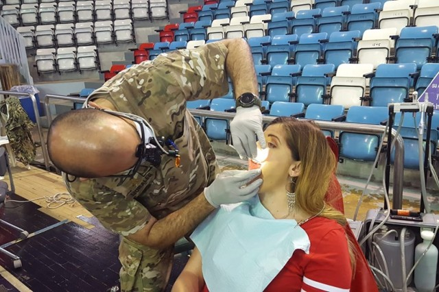 Maj. Jesus Morales, a dentist, from the 49th Multifunctional Medical Battalion, U.S. Army Reserve-Puerto Rico, conducts a dental examination on Ellinet Lopez Rivera, a local resident, during the Innovative Readiness Training mission at the city's sport complex, May 3.