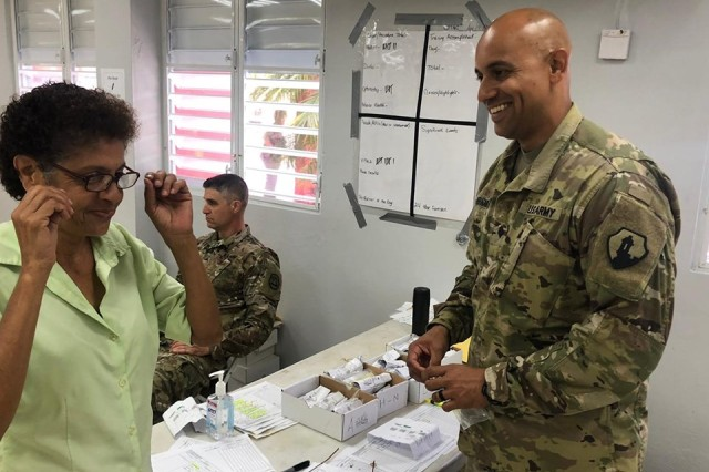 Spc. Hernán Hernández Santos, from the 49th Multifunctional Medical Battalion, U.S. Army Reserve-Puerto Rico, provides a new pair of glasses to Celeste Rodriguez, a patient at the town's event center, as part of the Innovative Readiness Training, May 3.