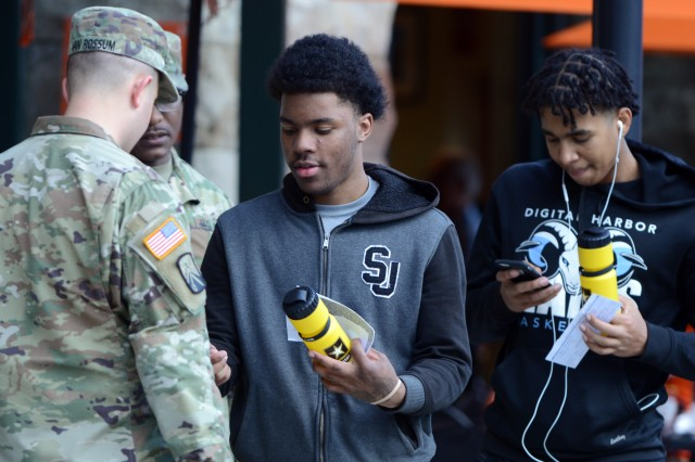 Sgt. Chobie Van Rossum (left) and Staff Sgt. Antwon Yourse of the Baltimore Recruiting Company hand out water bottles as they discuss opportunities in the Army with young fans attending an Orioles game May 3, 2019.