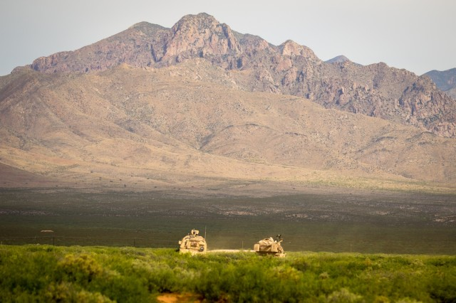 An M109A6 Paladin howitzer self-propelled gun and an M992 ammunition supply vehicle belonging to 4th Battalion, 27th Field Artillery Regiment, 2nd Armored Brigade Combat Team, 1st Armored Division, overlook a range, preparing to locate and engage a simulated target during Table XVIII gunnery qualification at Dona Ana Range Camp, N.M. May 7. The M109A6 Paladins belonging to 4-27 FA will collectively locate and fire at targets during the training event to ensure that their projectiles reach and hit the target at the same time, an artillery task referred to as time on target. Table XVIII gunnery is the culminating qualification event for the Iron Soldiers of 4-27 FA, consisting of several live-fire missions emphasizing coordination, precision and lethality, and preparing the battalion for two collective training exercises: Iron Focus 19.1 in June and a rotation at the National Training Center later this year.