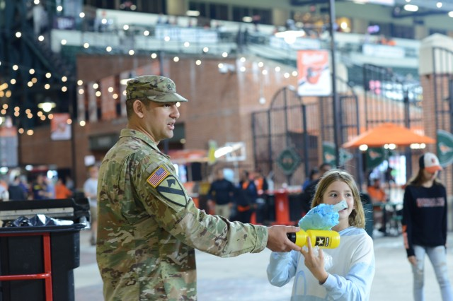 Staff Sgt. Bryan Lenis of the Baltimore Recruiting Company hands an Army water bottle to a young fan at the Eutaw Street concessions of Camden Yards during an Orioles game May 3, 2019.