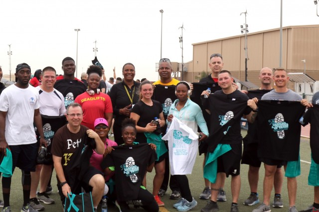 Soldiers pose with their shirts after the Sexual Harassment/Assault Response and Prevention program 5K run, sponsored by the 1st Theater Sustainment Command, at Camp Arifjan, Kuwait, April 1, 2019. (U.S. Army National Guard photo by Sgt. Connie Jones)