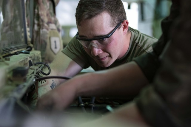 Spc. Dylann Farley, a wheeled vehicle mechanic from Echo Company, 1st Engineer Battalion, 1st Infantry Division, works on attaching a wire harness as part of a humvee engine swap, May 9, 2019 in Camp Karliki, Poland. Echo Company Soldiers have been working tirelessly to keep the Diehard Battalion running strong, since arriving in Poland. (U.S. Army photo by Sgt. Thomas Mort)
