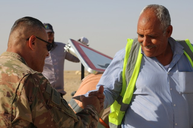 U.S. Army Sgt. 1st Class Al Gagow, 184th Sustainment Command, and senior Kuwait work crew worker fist bump during a traffic safety sign setup initiative conducted along routes in the vicinity of Camp Buehring, Kuwait, May 11, 2019. (U.S. Army photo by Sgt. Nahjier Williams)