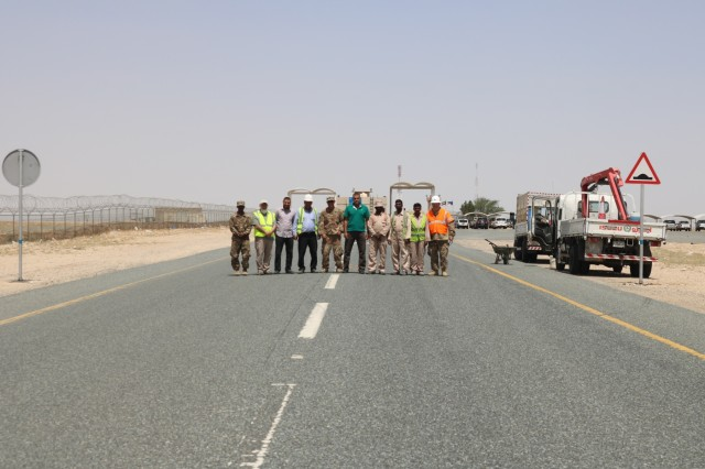 Members of the 1st Theater Sustainment Command and a Kuwait work crew stand for a photo in between two recently installed traffic signs during a traffic safety sign setup initiative conducted along routes in the vicinity of Camp Buehring Kuwait, May 11, 2019. (U.S. Army photo by Sgt. Nahjier Williams)
