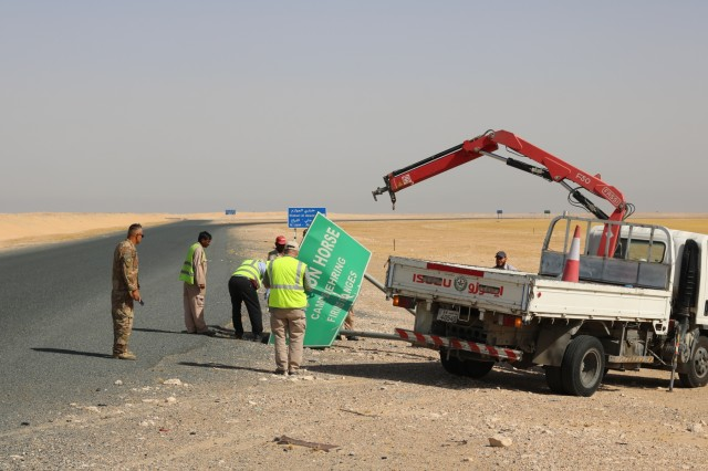 A Kuwait work crew attempts to reconstruct a damaged Camp Buehring road sign during a traffic safety sign setup initiative conducted along routes in the vicinity of Camp Buehring, Kuwait, May 11, 2019. (U.S. Army photo by Sgt. Nahjier Williams)