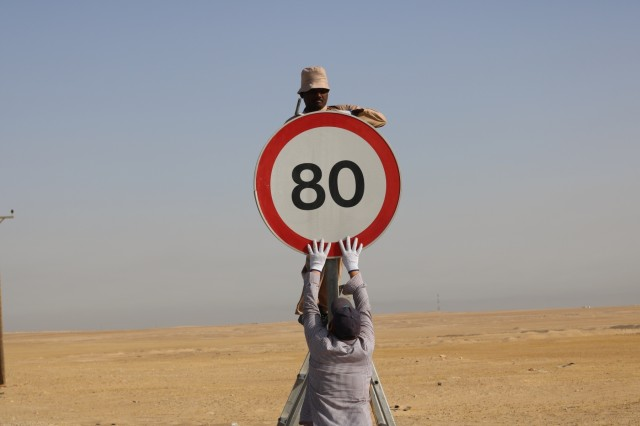 A Kuwait work crew reassembles a speed limit sign found detached from its pole during a traffic safety sign setup initiative conducted along routes in the vicinity of Camp Buehring, Kuwait, May 11, 2019. (U.S. Army photo by Sgt. Nahjier Williams)