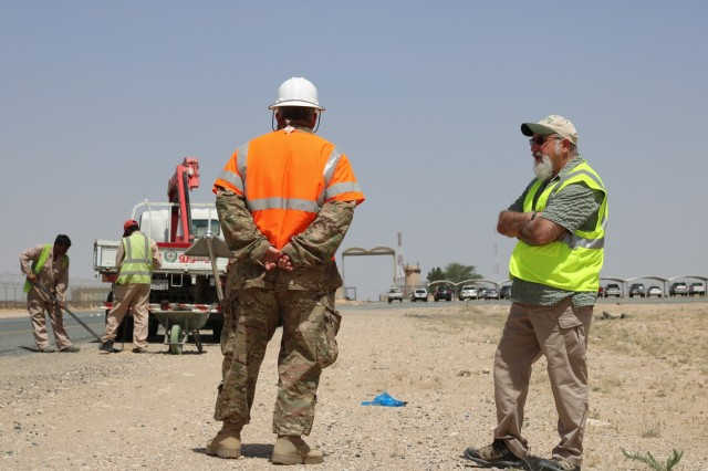 U.S. Army Chief Warrant Officer 3 David Hardigree, 184th Sustainment Command safety officer, and Mic Eargle, 1st Theater Sustainment Command safety director, observe workers during a traffic safety sign setup initiative conducted along routes in the vicinity of Camp Buehring, Kuwait, May 11, 2019. (U.S. Army photo by Sgt. Nahjier Williams)