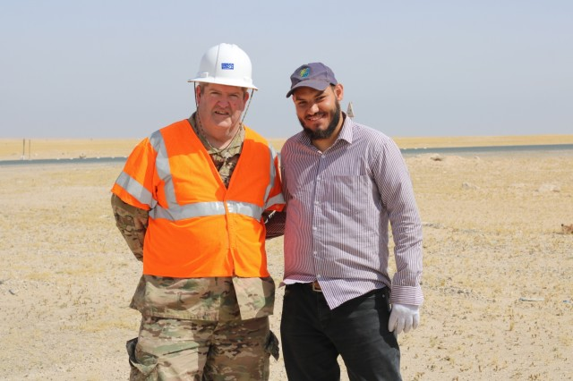 U.S. Army Chief Warrant Officer 3 David Hardigree, 184th Sustainment Command safety officer, stands with a Kuwait work party member during a traffic safety sign setup initiative conducted along routes in the vicinity of Camp Buehring, Kuwait, May 11, 2019. (U.S. Army photo by Sgt. Nahjier Williams)