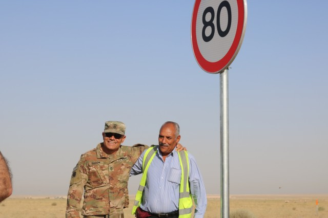 U.S. Army Sgt. 1st Class Al Gagow, 184th Sustainment Command, and a Kuwait work crew supervisor stand in front of recently installed speed limit sign during a traffic safety sign setup initiative conducted along routes in the vicinity of Camp Buehring Kuwait, May 11, 2019. (U.S. Army photo by Sgt. Nahjier Williams)