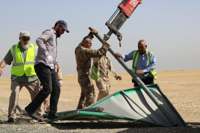 Members of the 1st Theater Sustainment Command work with Kuwait workers to bend a Camp Buehring road sign back into shape during a traffic safety sign setup initiative conducted along routes in the vicinity of Camp Buehring, Kuwait, May 11, 2019. (U.S. Army photo by Sgt. Nahjier Williams)