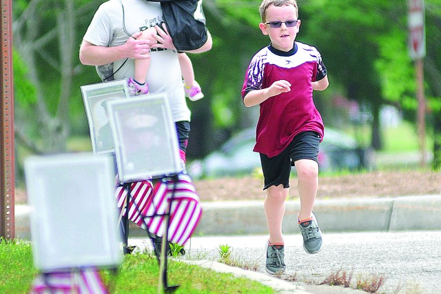 Seven-year-old family member Clayton Porter, son of Capt. Kevin Porter, rushes to the finish line during the Run for the Fallen May 11 at Williams Stadium.