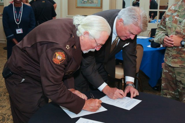"""FORT BENNING, Ga. -- Harris County, Alabama, Sheriff Mike Jolley, left, and Columbus, Georgia, Mayor B. H. """"Skip"""" Henderson sign a mutual aid agreement with Fort Benning, Georgia, and other area communities. If Fort Benning ever faces an emergency where it might need extra help from local governments and emergency responders, it'll be able to ask that help from numerous area communities -- and in turn give it if called upon -- under a mutual aid agreement signed here May 14. (U.S. Army photo by Markeith Horace, Maneuver Center of Excellence, Fort Benning Public Affairs Office)"""