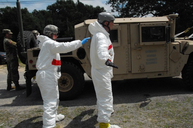 Spc. Autumn Rolland, from Wasilla, Alaska, checks the Tyvek protective suit of an FBI technician for any rips or tears during Prominent Hunt 19-1 in Mobile, Alabama. Prominent Hunt 19-1 is part of regularly scheduled biannual interagency training exercises by the U.S. government's National Technical Nuclear Forensics (NTNF) Ground Collection Task Force (GCTF) that have been conducted since 2012. This training exercise provides an opportunity to practice and enhance the NTNF GCTF's operational readiness to respond to a nuclear detonation in the United States or overseas.
