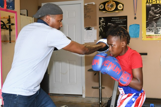 "Pryce Sparrow works ''the mitts"" with his father/coach, Kelvin Sparrow during his training for the Junior Olympic Regionals in Toledo, Ohio over Memorial Day weekend.Ryan Lewis, a sports director with Fort Knox said that Coach Sparrow and Youth Sports and Fitness Boxing Training Academy will conduct their first boxing camp July 15-19 which will be open to children aged 3-18 who are registered with Child & Youth Services. The non-contact camp will focus on the skills and conditioning needed to succeed in boxing"