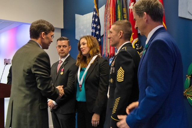 Secretary of the Army Mark T. Esper congratulates Rachel J. Phillips, 66th Military Intelligence Brigade sexual assault response coordinator after presenting her with the Army Meritorious Civilian Service Medals for her outstanding work educating a population identified as the most vulnerable to sexual harassment and sexual assault during the 2018 Department of Defense Advancing Primary Prevention Award during a Sexual Assault Awareness Prevention Month (SAAPM) Ceremony in the Hall of Heroes at the Pentagon, April 23. Phillips received the 2018 DoD Recognition for Advancing Primary Prevention award.