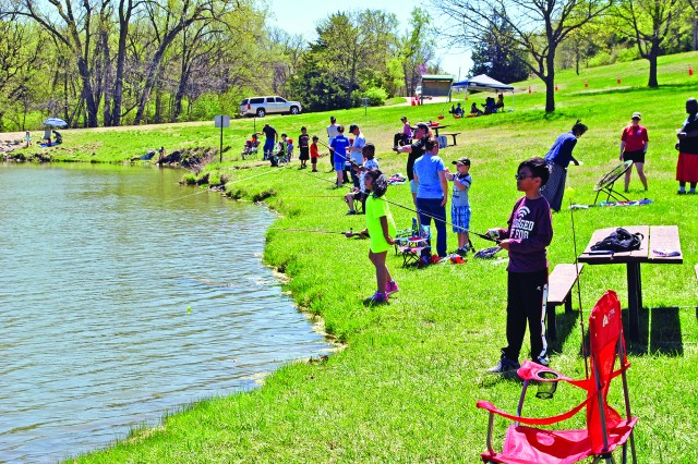 Families line the shore of Moon Lake during the Kids Fishing Day event April 20.