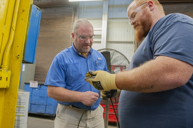 Chris Stanbaugh, right, discusses findings from an electrical inspection with John Rogers, a depot safety engineer. Employees should inspect all cords and outlets prior to use to avoid electrical hazards.