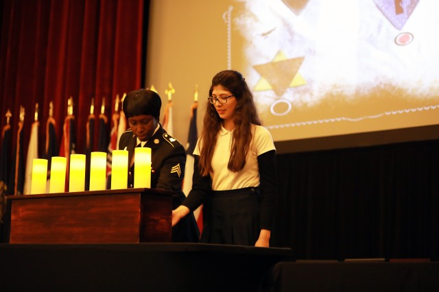 Sgt. Sache Taylor, 512th Engineer Detachment is joined by a Shmuel Bass Torah Academy of San Antonio student to light a candle during the Joint Base San Antonio-Fort Sam Houston's Day of Remembrance to honor those affected by the Holocaust on May 2.