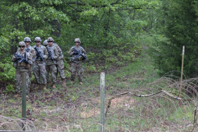 Soldiers line up to demonstrate a route clearance usage of the Bandolier, which lays across barbed wire during MSSPIX, May 9, at Fort Leonard Wood, Mo.