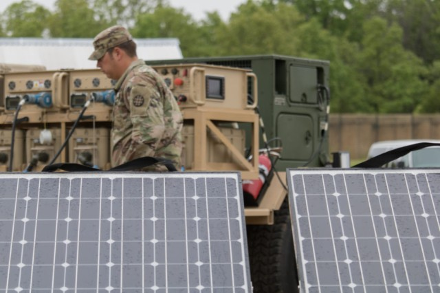 A Soldier walks behind solar panels attached to the Mobile Electric Hybrid Power Sources, which uses both solar energy and fuel to generate power on the battlefield during MSSPIX, May 9, at Fort Leonard Wood, Mo.