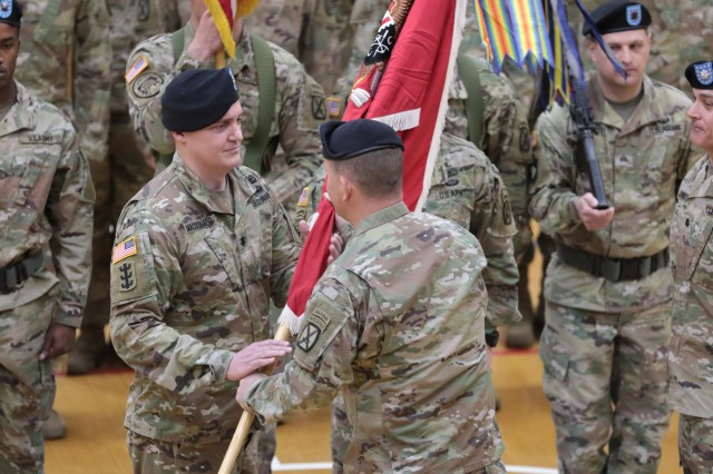 Lt. Col. Glen A. MacDonald, a native of South Windsor, Connecticut, receives the battalion colors from Col. Shane Morgan, the 1st Brigade Combat Team, 10th Mountain Division commander, during a change of command ceremony on Fort Drum, New York on May 6.
