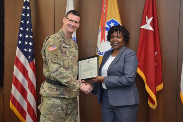 Sheyla Ware accepts the Employee of the Quarter award from Maj. Gen. Jeff Drushal, commander of the U.S. Security Assistance Command, during a town hall ceremony April 8.