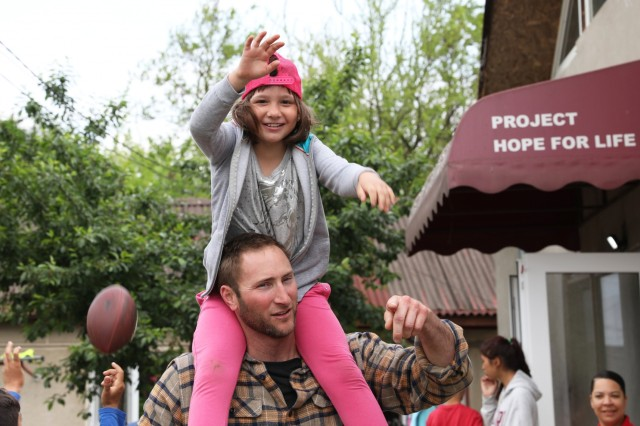 A service member lifts a girl on his shoulders at Project Romania Rescue's Casa Benjamin in Valu Lui Traian, Romania May 18 2019. About a dozen service members stationed at Mihail Kogalniceanu Air Base, Romania visited Project Romania Rescue, an orphanage and community service center, to spend time with the children and engage with the community. U.S. Army photo by Sgt. Erica Earl