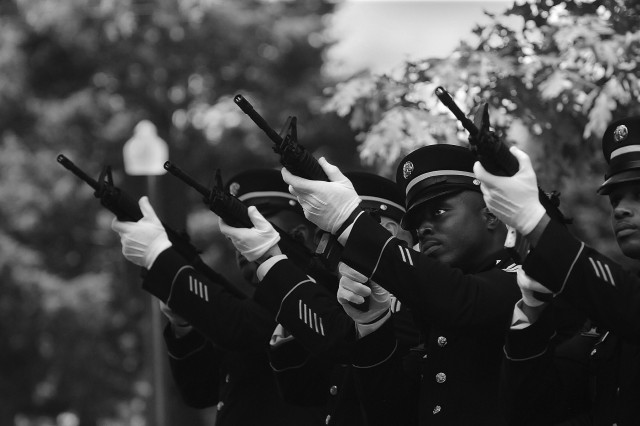 Members of an honor guard fire volleys during a memorial service at Memorial Chapel honoring Col. Gregory Townsend, who was fatally injured April 18 during a car repair incident.
