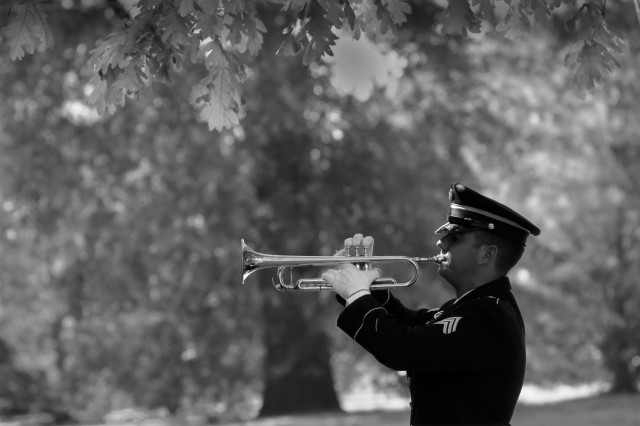 """Sgt. Elliot Mee, 392nd Army Band trumpeter, plays """"Taps"""" during a memorial service honoring Col. Gregory Townsend April 30 at Memorial Chapel."""