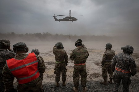 U.S. Army National Guard Soldiers from New Jersey's 250th Brigade Support Battalion look on as a UH-60M Black Hawk helicopter carries a sling load on Joint Base McGuire-Dix-Lakehurst, N.J., May 4, 2019.