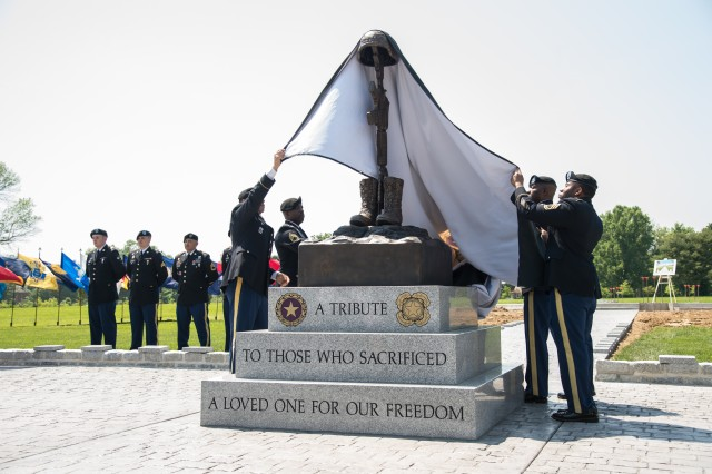 Aberdeen Proving Ground noncommissioned officers gracefully unveil the new Legacy Forest Gold Star Memorial at Plum Point during the ceremony preceding the Gold Star Spouses & Family Tea at Top of the Bay, May 19, 2019.