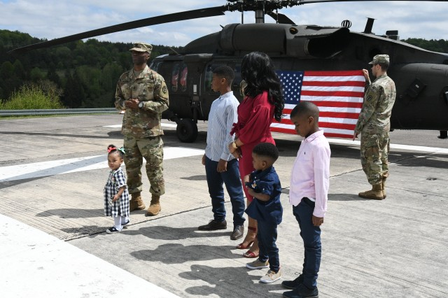 With his youngest daughter standing in front of him, newly promoted Capt. Eric S. Anderson Sr. (left), executive officer for the U.S. Army Health Clinic Hohenfels, speaks to family, friends, clinic staff and senior leadership at his promotion ceremony, May 17, 2019, at the AHC Hohenfels Clinic Helipad, Hohenfels, Germany. Anderson was diagnosed with having chronic lymphocytic leukemia, or CLL, a type of cancer in which the bone marrow makes too many lymphocytes, a type of white blood cell. CLL is one of the most common types of leukemia in adults. Anderson, a native of Fort Worth, Texas, is being assigned as a patient at Brooke Army Medical Center Warrior Transition Battalion at Joint Base San Antonio-Fort Sam Houston, Texas. His family will accompany him to Texas. (U.S. Army photo by Alain M. Polynice)