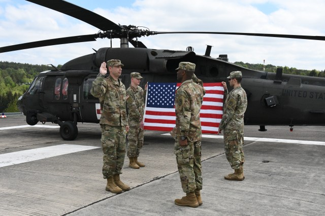 Lt. Col. Sam Preston (left), U.S. Army Health Clinic Hohenfels commander, administers the oath of commissioned officers to newly promoted Capt. Eric S. Anderson Sr., AHC Hohenfels executive officer, May 17, 2019, at the AHC Hohenfels Clinic Helipad, Hohenfels, Germany. Anderson was diagnosed with having chronic lymphocytic leukemia, or CLL, a type of cancer in which the bone marrow makes too many lymphocytes, a type of white blood cell. CLL is one of the most common types of leukemia in adults. Anderson, a native of Fort Worth, Texas, is being assigned as a patient at Brooke Army Medical Center Warrior Transition Battalion at Joint Base San Antonio-Fort Sam Houston, Texas. His family will accompany him to Texas. (U.S. Army photo by Alain M. Polynice)