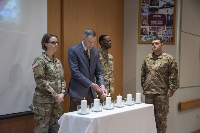 Dr. Steven Rosenblatt, guest speaker, lights a candle to honor the 6 million Jews killed during the Holocaust May 15, 2019 during the Days of Remembrance observance at Brooke Army Medical Center, Joint Base San Antonio, Texas. Rosenblatt, the son of a Holocaust survivor, talked about Adolf Hitler's rise to power and his mother's journey as a Holocaust survivor.