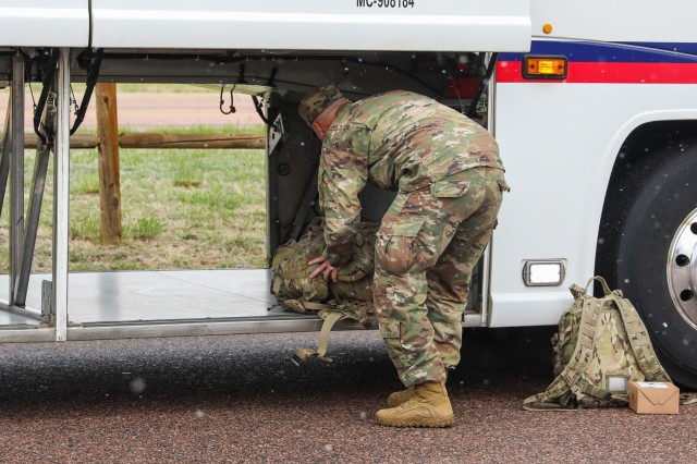 A U.S. Army Soldier assigned to 2nd Battalion, 12th Infantry Regiment, 2nd Infantry Brigade Combat Team, 4th Infantry Division, stores his bag under a bus, May 9, 2019, as he and the rest of the 2nd Bn., 12th Inf. Reg. Soldiers prepare to depart Fort Carson, Colorado in support of Cadet Summer Training at Fort Knox, Kentucky. (U.S. Army photo by Staff Sgt. Neysa Canfield)