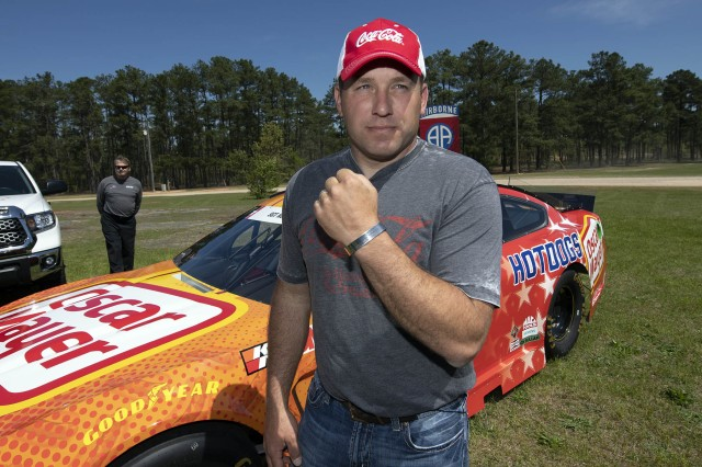 NASCAR driver Ryan Newman shows a bracelet given to him by Gold Star Family member Jamie Nolen at Fort Bragg, N.C., April 17, 2019. The bracelet is engraved with the name of Jamie's father, Army Sgt. James Nolen, whose name is also on Newman's car behind him.