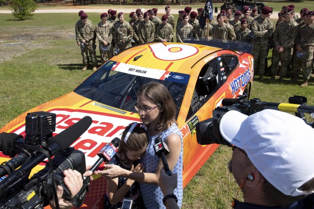 Gold Star Family member Jamie Nolen hangs onto her mother, Rachel, as reporters ask them about NASCAR driver Ryan Newman's car being dedicated to Army Sgt. James Nolen at Fort Bragg, N.C., April 17, 2019. James Nolen died while serving in Afghanistan in 2009.