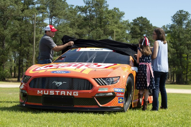 NASCAR driver Ryan Newman and Gold Star Family members Rachel and Jamie Nolen unveil Newman's car dedicated to Army Sgt. James Nolen at a dining facility at Fort Bragg, N.C., April 17, 2019. James Nolen died while serving in Afghanistan in 2009.