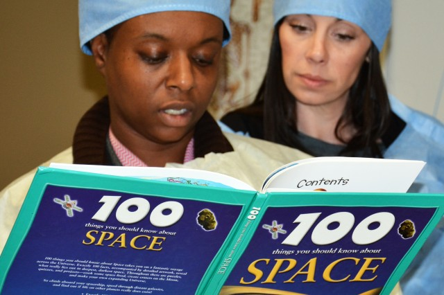 Labreshawn Davis, a medical support assistant, and Vicky Dailey, a registered nurse, pour over a space reference book to learn about the planet Jupiter.  Both are from the Urology Department and participated in Carl R. Darnall Army Medical Center's Escape Room challenge, held May 7 in honor of National Nurses Week.