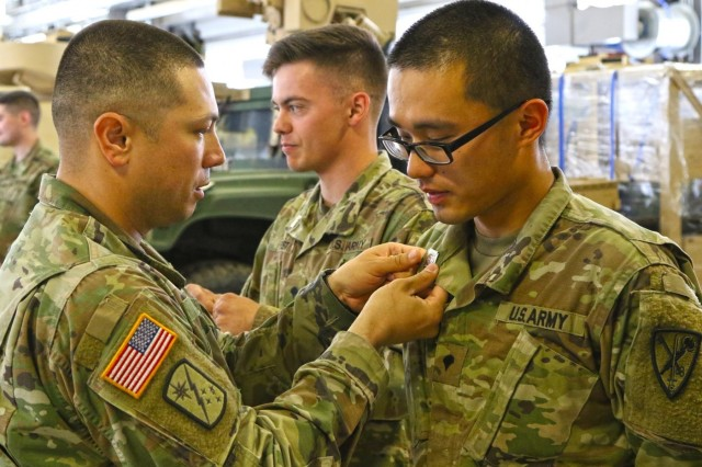 Staff Sgt. Ryan Forgey, motor sergeant, 504th Military Police Battalion, pins a driver and mechanic badge on Spc. Zhengyang Rao during the battalion's Enabler Appreciation Day. Often working behind the scenes to keep the 504th Military Police Battalion on the road and able to deploy, the battalion held an Enabler Appreciation Day to show their thanks to the maintainers, medics and communicators who make their missions possible. The USO Northwest Chapter was at the event providing food and drinks.
