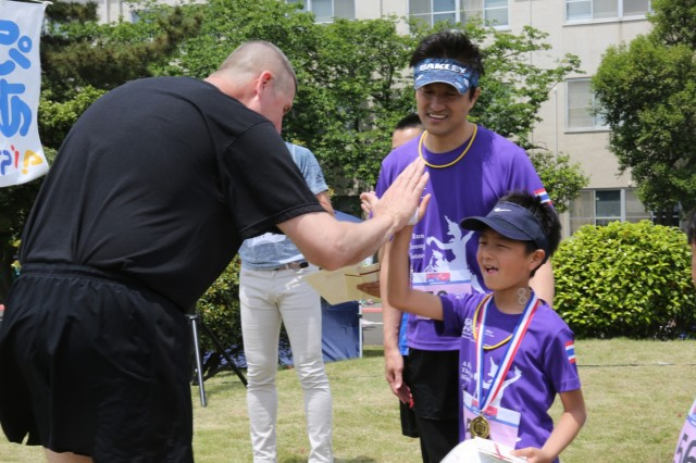 Lt. Col. Gary Whittacre, commander of the 836th Transportation Battalion, gives a high five to a runner at the award ceremony for the Yokohama North Dock Running Festival May 18, which Whittacre's unit hosted along with Camp Zama's Family, Morale, Welfare and Recreation.