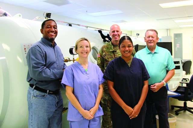 The staff of the Hyperbaric Medicine Clinic at Eisenhower Army Medical includes Emanuel Stephens, left, certified hyperbaric technician; Teresa Kitchens, advanced clinical hyperbaric registered nurse; Spc. Nicole Cruz, NCOIC; Col. Jonathan Stabile, OIC; and Herb Yeager CHT, hyperbaric safety director, gather outside EAMC's  hyperbaric chamber which is a dual-lock, multiplace chamber, capable of treating up to 12 patients simultaneously. (Photo by David M. White/RELEASED)