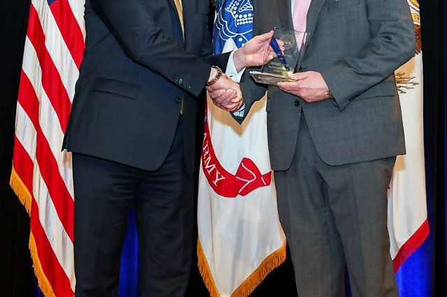 Under Secretary of the Army Ryan McCarthy (left) presents Bruce Cotton with his award for Secretary of the Army's 2018 Editor of the Year Award, Command Publication category, during a ceremony May 3 at the Pentagon. Cotton is managing editor of PS Magazine. (Photo by Spc. James Harvey, Army Multimedia & Visual Information Directorate)